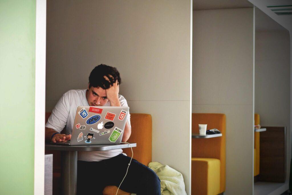 パソコン画面を見て頭を抱える男