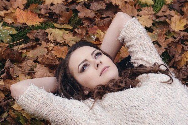 落ち葉の下で考える女性
