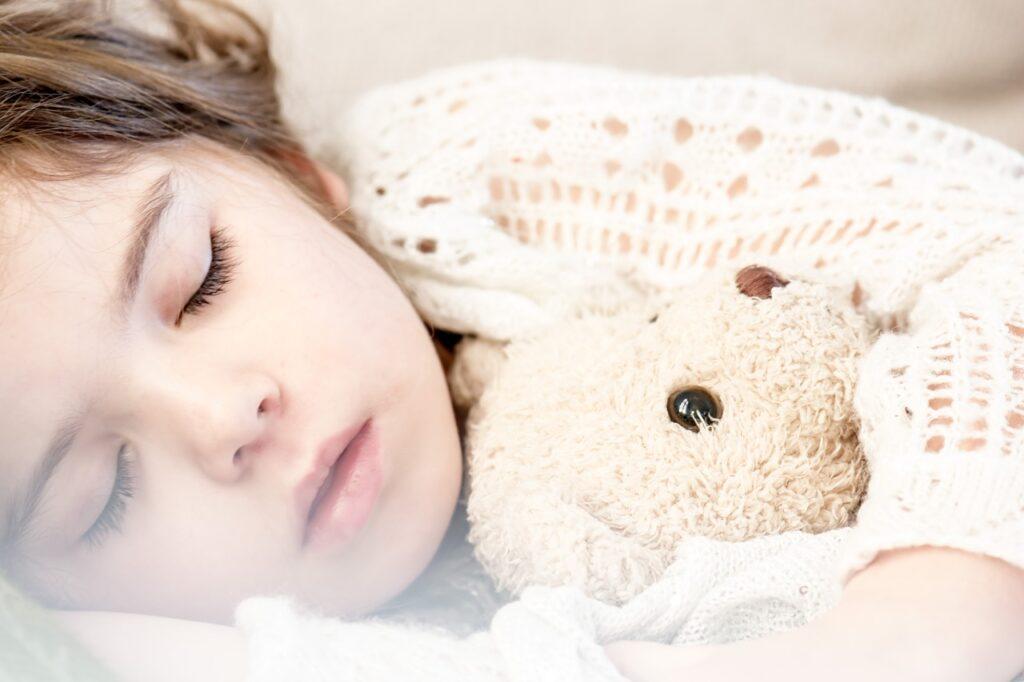 クマのぬいぐるみを抱いて眠る少女