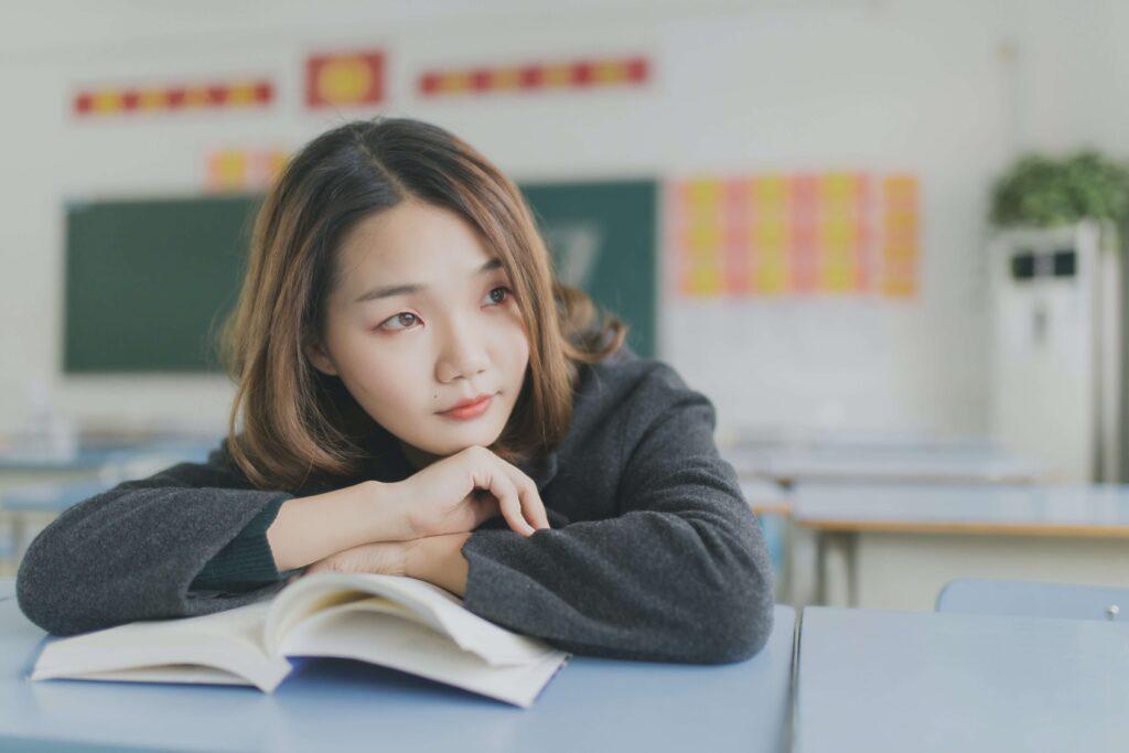女学生が教科書を開いて座っている