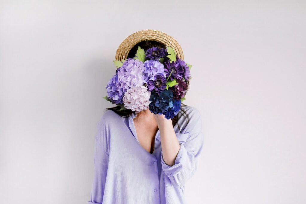 花で顔を隠す女性