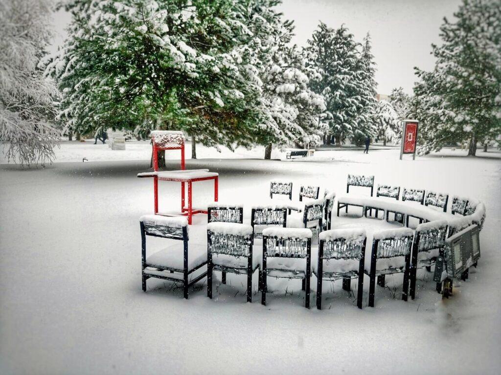 雪が積もり外に椅子が並べてある画像
