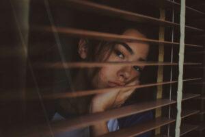 窓の様子を見る女性