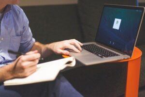 PCで作業をしてメモを取る男性