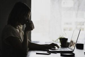 PCに向かってコーヒーを飲む女性